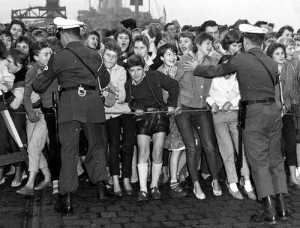 Young fans of Elvis Presley are trying to get closer to their hero when he arrived in Bremerhaven on Oct. 1, 1958. The military police is hindering the people in breaking the barricades. Presley came to Germany on the occasion of his Army service which he will spend at Friedberg in the Wetterau near Frankfurt am Main. (10/01/1958)(AP Photo/Brueg)